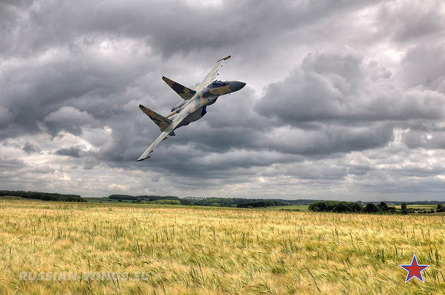 Su-35 carving over cornfields